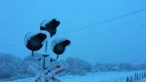 Traffic lights at a railway crossing in winter. The Traffic lights at a railway crossing in winter stock video footage