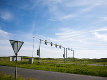 Traffic lights and sign against a blue sky. Traffic lights and a give way sign on parallel roads and a blue sky Stock Photography