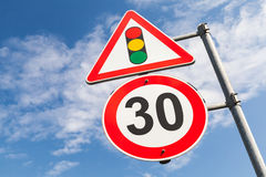 Traffic lights and speed limit 30 km per hour. Mounted on metal post. Road signs over blue sky background Stock Image