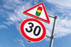 Traffic lights and speed limit 30 km per hour. Mounted on one metal post. Road signs over blue sky background Royalty Free Stock Photo
