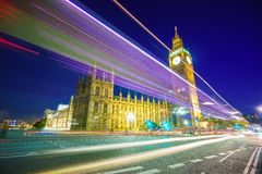 Traffic through London. Big Ben and houses of parliamen in London, UK at night with moving red double-decker bus leaving light traces. Traffic Through London ( Royalty Free Stock Image