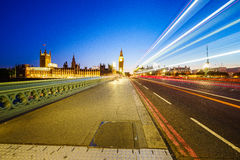 Traffic through London. Big Ben and houses of parliamen in London, UK at night with moving red double-decker bus leaving light traces. Traffic Through London ( Royalty Free Stock Photo