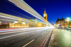 Traffic through London. Big Ben and houses of parliamen in London, UK at night with moving red double-decker bus leaving light traces. Traffic Through London ( Royalty Free Stock Photography