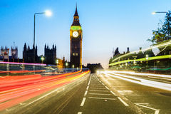 Traffic through London. Big Ben and houses of parliamen in London, UK at night with moving red double-decker bus leaving light traces. Traffic Through London ( Stock Photos