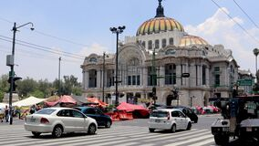 Traffic in Mexico City on Lázaro Cárdenas avenue with the palace of fine arts in the background