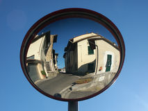Traffic mirror reflecting small town Stock Photography