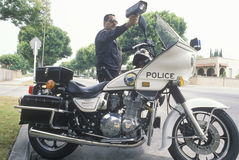 Traffic motorcycle cop pointing radar gun, Royalty Free Stock Photos