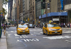 Traffic in New York City with famous yellow-coloured taxi cabs passing by Royalty Free Stock Image