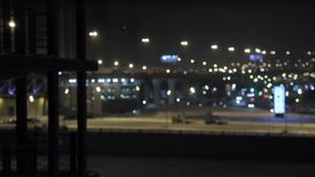 Traffic in night city, cars drive, defocused and blurred video, bokeh urban lights scene. Gimbal shot of moving cars traffic at night. Building works and stock video