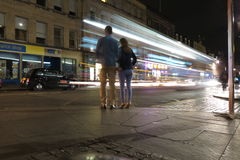 Traffic at night in the city of Edinburgh in Edinburgh. EDINBURGH, UK - CIRCA AUGUST 2015: Traffic at night in the city of Edinburgh with a couple waiting to Stock Image