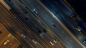 Traffic on night highway. Road intersection view from above. Drone footage of city roads and highways at night. View from above. 4K stock footage