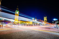 Traffic at night in London. Big Ben and houses of parliamen in London, UK at night with moving red double-decker bus leaving light traces. Traffic Through London Royalty Free Stock Images