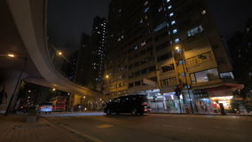 Traffic in night street of Hong Kong. HONG KONG - NOVEMBER 09, 2015: Transport traffic on night city street with high-rise apartment blocks stock video footage