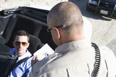Traffic Officer Checking Man's License Stock Photo