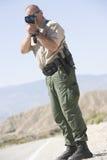 Traffic Officer Monitoring Speed Through Radar Gun Royalty Free Stock Images