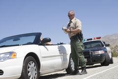 Traffic Officer Writing Ticket. Full length of a mature traffic officer writing ticket Royalty Free Stock Photography