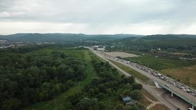 Drone Point of view - aerial view of rush hour traffic jam highway. Traffic at peak hour with cars on the road, over the bridge stock footage