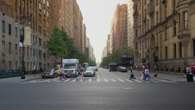 Traffic and pedestrians on Manhattan intersection and crosswalk. New York City - circa October, 2017 - An early morning establishing shot of traffic and stock video