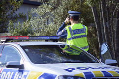 Traffic Police officer. AUCKLAND,NZ - JUNE 03 2014:Traffic Police officer pointing his radar gun at speeding traffic.Traffic Police Monitor traffic to ensure Stock Image