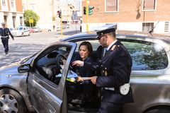 Traffic police officer checks documents of female driver on the streets of Rome. Italy, Rome - April , 28, 2013: A traffic police officer checks documents of a Royalty Free Stock Image
