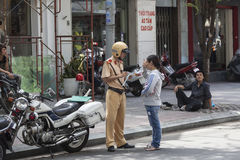 Traffic police on the street of Ho Chi Minh. Policeman giving ticket to woman because she did not have helmet while driving Stock Photo