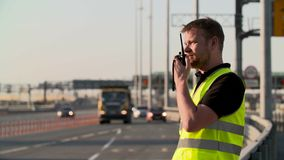 Traffic police with walkie talkie work at highway