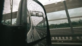 Traffic in Rain from rearview mirror, Driving Car, Storm on Road, Highway, Rainy Drops in slow motion. Traffic in Rain rearview mirror, Driving Car, Storm on stock video footage