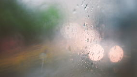Traffic in rain. A view through the window of a moving tram with rain on the outside. Shallow DOF, focus on raindrops on the window stock footage