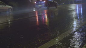 Traffic in rainy day in the city. View from the level of asphalt level. Selective focus on the wet road.  stock footage