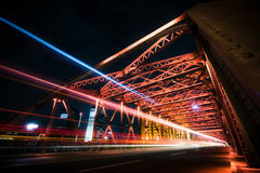 Traffic on red steel bridge at night. Light trails of vehicles crossing a steel bridge at night. The bridge is illuminated by red lights Stock Image