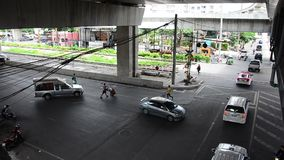 Traffic road with cars driving and people walking cross over road. BANGKOK, THAILAND - SEPTEMBER 14 : Traffic road with cars driving and people walking cross stock video footage