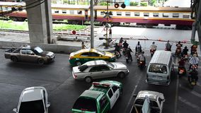 Traffic road and cars stopping wait train running pass cross over road. BANGKOK, THAILAND - SEPTEMBER 14 : Traffic road and cars stopping wait train running pass stock video