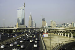 Traffic on roadway in Dubai, UAE. Traffic driving into Dubai city in the United Arab Emirates on sunny day Royalty Free Stock Images