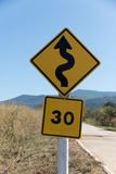 Traffic S-Curves Sign. A Traffic sign warns of sharp turns ahead and speed limit on a road royalty free stock images