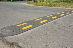 Traffic safety speed bump on an asphalt road. Speed bumps or speed breakers are traffic calming devices. Traffic safety speed bump on an asphalt road. Speed stock photos