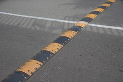 Traffic safety speed bump on an asphalt road. Road bumps for reduce speed stock images