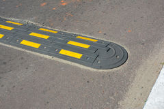 Traffic safety speed bump on an asphalt road. Speed bumps (or speed breakers). Are the common name for a family of traffic calming devices stock image