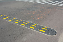 Traffic safety speed bump with crosswalk on an asphalt road. Speed bumps (or speed breakers). Are the common name for a family of traffic calming devices royalty free stock photos