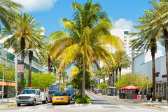 Traffic and shops among tropical palm trees at Lincoln Road in. MIAMI,USA - MAY 20,2014 : Traffic and shops among tropical palm trees at Lincoln Road, a famous royalty free stock photography