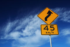 Traffic Sign. Curved Road Traffic Sign over Blue Sky royalty free stock image