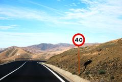 A Traffic Sign Along A Lonesome Road With Serpentines. One of the many beautiful roads along the coast of the canary islands Stock Photo