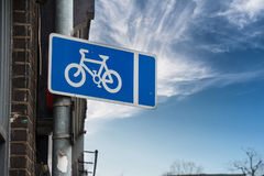 Traffic Sign: Blue-White Bicycle. Traffic Sign: White Bicycle on Blue Banner with Bright Sky background Royalty Free Stock Photo