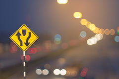 Traffic sign and defocused lights bokeh as light car on road bac Royalty Free Stock Images