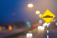 Traffic sign and defocused lights bokeh as light car on road bac Royalty Free Stock Photo