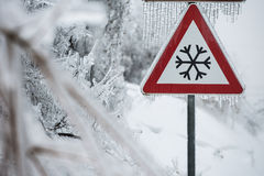 Traffic sign for icy road with sleet covered trees. Danger on the road, black ice danger, wintertime concept Royalty Free Stock Image