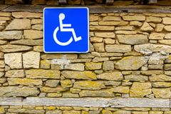 Stone wall and disabled access Sign, handicap accessible sign. Traffic sign indicating parking for persons with disabilities hanging on rough stone wall Royalty Free Stock Photos
