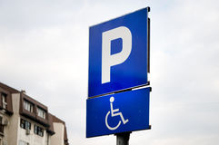 Traffic sign indicating a parking place and a place for people with disabilities with cars Royalty Free Stock Photo