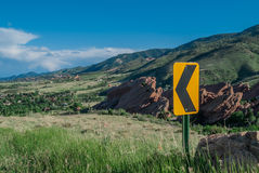 Traffic Sign in Mountains. A yellow and black sign directs traffic in the foothills of the Rocky Mountains stock photos