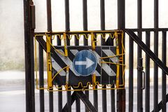 Traffic sign one way street sign with protective security fence / Metal fence with traffic sign arrow blue. Traffic sign one way street sign with protective stock photo