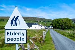 Traffic sign for paying attention for elderly. People at the entrance of a small Scottish village Stock Photo